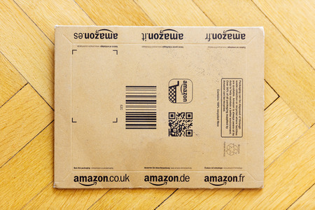 Small Amazon box used for books and other small object delivery with Amazon.com, Amazon.it, Amazon.de, Amazon.co.uk, Amazon.fr, Amazon.es. Amazon is an American electronic e-commerce company distribution worlwide Editorial