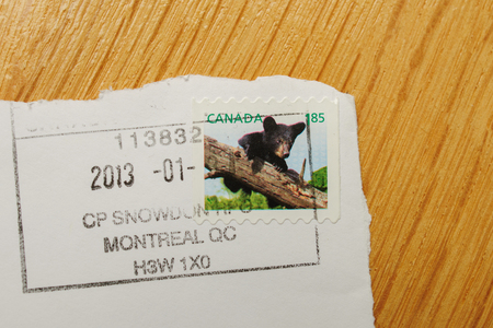 qc: PARIS, FRANCE - DEC 30, 2013: Franked postage stamp with Canadian bear issued by Canada Post