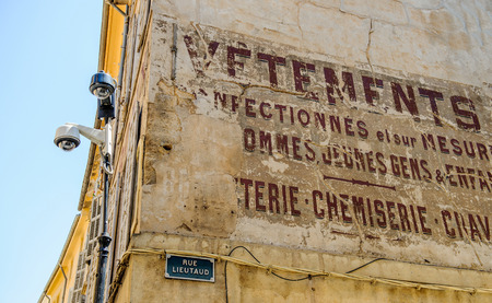 rue: AIX-EN-PROVENCE, FRANCE - JUL 17, 2014: Old inscription on building of a store selling clothes with the street name Rue Lieutad and two security camera surveilling the city Editorial