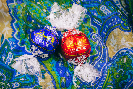 lindt: KILCHBERG, SWITZERLAND - MAR 20, 2014: Tasty red Lindt Lindor chocolate on a colored silk background, Lindt AG, more commonly known as Lindt, is a Swiss chocolatier and confectionery company founded in 1845 and known for their chocolate truffle balls and  Editorial