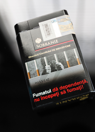 redstone: FRANKFURT, GERMANY - SEP 22, 2016: Sobranie cigarettes pack on glass table with inscription Quit Smoking Now in Romanian langauge. The Sobranie cigarette brand is one of the oldest luxury tobacco brands in the world. Sobranie of London was established in  Editorial
