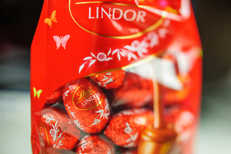 lindt: KILCHBERG, SWITZERLAND - MAR 20, 2014: Tasty Lindt Lindor chocolate in box ready for Christmas holidays. Lindt AG, more commonly known as Lindt, is a Swiss chocolatier and confectionery company founded in 1845 and known for their chocolate truffle balls a Editorial