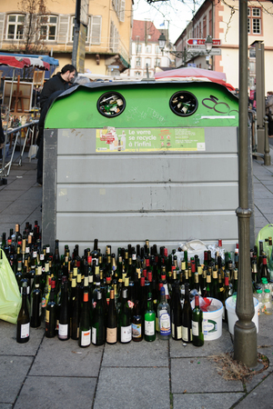 public waste: STRASBOURG, FRANCE -  DEC 15, 2013: Multiple wine and beer bottles near glass recycle bin in urban enviroment in the french city of Strasbourg, France