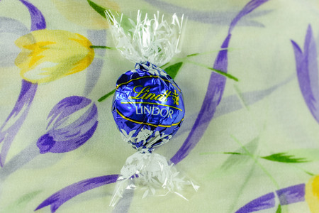 ag: KILCHBERG, SWITZERLAND - MAR 20, 2014: Tasty Lindt Lindor chocolate on a colored silk background, Lindt & Sprüngli AG, more commonly known as Lindt, is a Swiss chocolatier and confectionery company founded in 1845 and known for their chocolate truffle ba