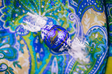 KILCHBERG, SWITZERLAND - MAR 20, 2014: Tasty blue Lindt Lindor chocolate on a colored silk background, Lindt & Sprüngli AG, more commonly known as Lindt, is a Swiss chocolatier and confectionery company founded in 1845 and known for their chocolate truff