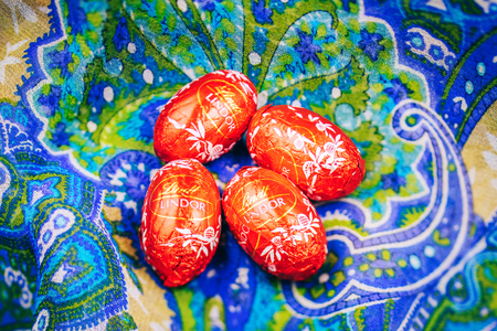 lindt: KILCHBERG, SWITZERLAND - MAR 20, 2014: Four Tasty Lindt Lindor chocolate on a colored silk background, Lindt & Sprüngli AG, more commonly known as Lindt, is a Swiss chocolatier and confectionery company founded in 1845 and known for their chocolate truff