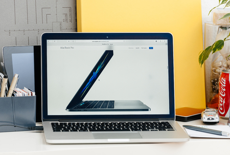 15 inch: PARIS, FRANCE - OCT 28 2016: Apple Computers website on new MacBook Pro Retina with OLED touch bar in a geek creative room showcasing new professional laptop - side view of the new 15 inch laptop in space gray