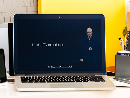 unified: PARIS, FRANCE - OCT 28 2016: Apple Computers website on new MacBook Pro Retina with OLED Touch bar in geek creative room showcasing Apple Keynote - Tim Cook about Unified TV experience Editorial