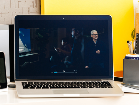 retina: PARIS, FRANCE - OCT 28 2016: Apple Computers website on new MacBook Pro Retina with OLED Touch bar in geek creative room showcasing Apple Keynote , Tim cook talking about the future of Apple TV