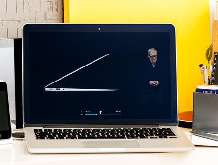 macbook pro: PARIS, FRANCE - OCT 28 2016: Apple Computers website on new MacBook Pro Retina with OLED Touch bar in geek creative room showcasing Apple Keynote Tim Cook talking about the MacBook Pro and its advantages