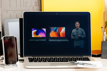 15 inch: PARIS, FRANCE - OCT 28 2016: Apple Computers website on new MacBook Pro Retina with OLED Touch bar in geek creative room showcasing Apple Keynote - Philip Schiller comparing new MacBook Pro