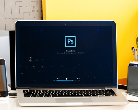 photoshop: PARIS, FRANCE - OCT 28 2016: Apple Computers website on new MacBook Pro Retina with OLED Touch bar in geek creative room showcasing Apple Keynote presentation of Bradee Evans from Adobe OLED Photoshop inegration