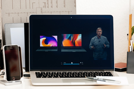 15 inch: PARIS, FRANCE - OCT 28 2016: Apple Computers website on new MacBook Pro Retina with OLED Touch bar in geek creative room showcasing Apple Keynote - Philip Schiller comparing new MacBook Pro Retina Editorial
