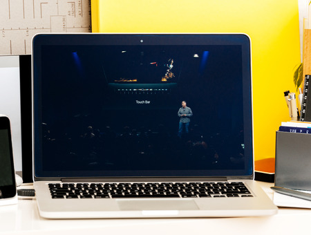 retina: PARIS, FRANCE - OCT 28 2016: Apple Computers website on new MacBook Pro Retina with OLED Touch bar in geek creative room showcasing Apple Keynote - Philip Schiller talking about new speccs, Touch Id, Oled Bar