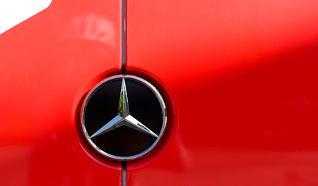 daimler: STRASBOURG, FRANCE - JUN 24 2016: Mercedes-Benz steel brand logo on a red van. Mercedes-Benz is a global automobile manufacturer and a division of the German company Daimler AG