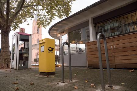cabina telefono: Kehl, Alemania - 18 de octubre, 2016: apartado de correos Deutsche Post DHL en ciudad con la mujer que llama desde la cabina de teléfono en la típica ciudad alemana