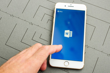 microsoft: PARIS, FRANCE - SEPT 26, 2016: New iPhone 7 Plus with hand touching screen to make a new Microsoft Word document on mobile phone. iPhone 7 and iPhone 7 plus is the most wanted phone worldwide