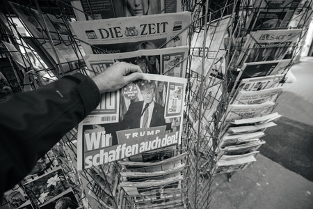 skepticism: PARIS, FRANCE - NOV 10, 2016: Man buying German newspaper Bild with shocking headline title at press kiosk about the US President Elections - Donald Trump is the 45th President of United States of America Editorial