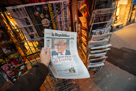 shocking: PARIS, FRANCE - NOV 10, 2016: Man buying Italian newspaper La Republica with shocking headline title at press kiosk about the US President Elections - Donald Trump is the 45th President of United States of America