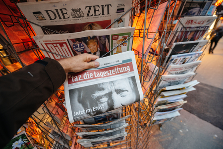 skepticism: PARIS, FRANCE - NOV 10, 2016: Man buying German newspaper Tag Die Tageszeitung with shocking headline title at press kiosk about the US President Elections - Donald Trump is the 45th President of United States of America Editorial