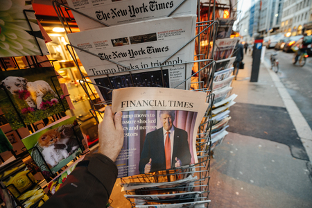 insecurity: PARIS, FRANCE - NOV 10, 2016: Man buying Financial Times newspaper with shocking headline title at press kiosk about the US President Elections - Donald Trump is the 45th President of United States of America