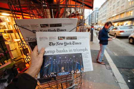 skepticism: PARIS, FRANCE - NOV 10, 2016: Man buying The New York Times newspaper with shocking headline title at press kiosk about the US President Elections - Donald Trump is the 45th President of United States of America