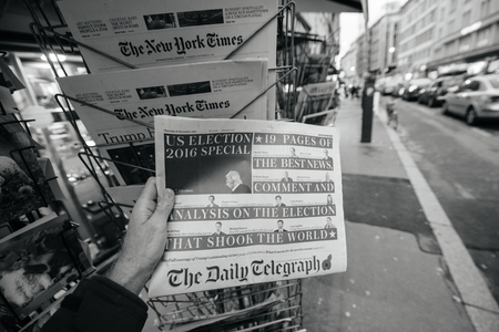 insecurity: PARIS, FRANCE - NOV 10, 2016: Man buying The Daily Telegraph newspaper with shocking headline title at press kiosk about the US President Elections - Donald Trump is the 45th President of United States of America