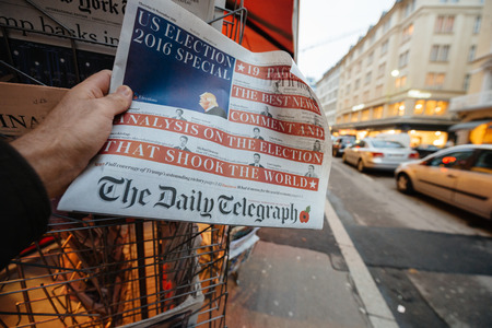 skepticism: PARIS, FRANCE - NOV 10, 2016: Man buying The Daily Telegraph newspaper with shocking headline title at press kiosk about the US President Elections - Donald Trump is the 45th President of United States of America