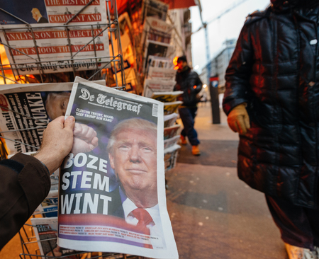 skepticism: PARIS, FRANCE - NOV 10, 2016: Man buying Dutch newspaper with De Telegraaf shocking headline title at press kiosk about the US President Elections - Donald Trump is the 45th President of United States of America Editorial