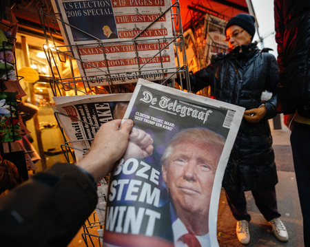 donald: PARIS, FRANCE - NOV 10, 2016: Man buying Dutch newspaper with De Telegraaf shocking headline title at press kiosk about the US President Elections - Donald Trump is the 45th President of United States of America Editorial