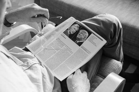 political economist: PARIS, FRANCE - NOV 10, 2016: Man reading The Economist magazine with Donald Trump aand Hillary Clinton after US President Election - Donald Trump is the 45th President of United States of America