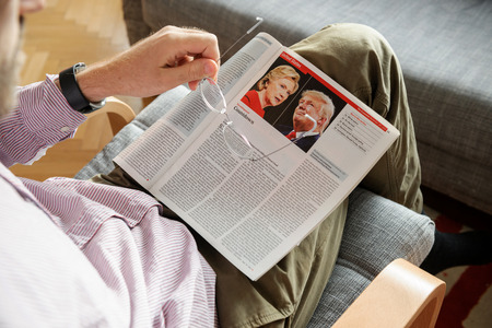 skepticism: PARIS, FRANCE - NOV 10, 2016: Man reading The Economist magazine with Donald Trump aand Hillary Clinton after US President Election - Donald Trump is the 45th President of United States of America