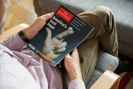 political economist: PARIS, FRANCE - NOV 10, 2016: Man reading The Economist magazine with America Best Hope cover illustrating US President Election - Donald Trump is the 45th President of United States of America