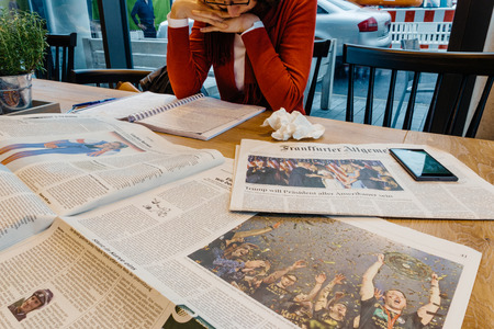 skepticism: PARIS, FRANCE - NOV 10, 2016: Woman reading in cafe Frankfurter Allgemeine Zeitung newspapper with Donald Trump elected as President as the 45th President of United States of America Editorial