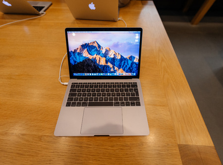 macbook pro: PARIS, FRANCE - NOV 10 2016: New latest MacBook Pro Retina with on wooden table. The fourth generation MacBook Pro was revealed on October 27, 2016. Phil Schiller described it as the Thinnest and lightest MacBook Pro ever