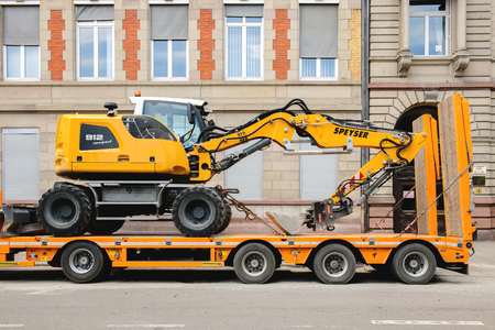mini loader: STRASBOURG, FRANCE - MAY 18, 2016: Liebherr 912 compact excavator on transportation trailer in urban environment with luxury apartment office historic building behind Editorial