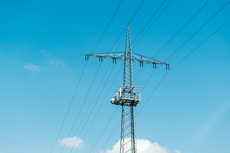 against the current: Electrical tower current mast against blue clear sky with  - advertising image for environmentally friendly energy producers