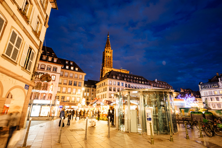 STRASBOURG, FRANCE - DEC 24, 2015: Christmas MArket stall with people shopping for traditional gifts and food mulled wine in Place Gutenberg