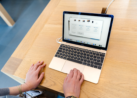 retina display: PARIS, FRANCE - SEP 12, 2016: Woman testing new Apple MacBook Pro Retina Laptop before buying it. MacBook Pro is ne of the most wanted laptop worldwide