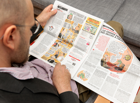 newsfeed: PARIS, FRANCE - NOV 12, 2016: Man reading Charlie Hebdo magazine on after Donal Trump elections as USA President - reading comics about French culture Editorial