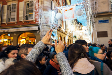 rue: STRASBOURG, FRANCE - DEC 06, 2015: taking a photo of the Christmas decorations with a mobile smartphone with the magic atmosphere on the Rue Des Orfevres in central Strasbourg