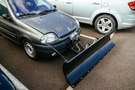 blanketed: STRASBOURG, FRANCE - CIRCA 2016:  Snow plow attached to a passenger Renault car