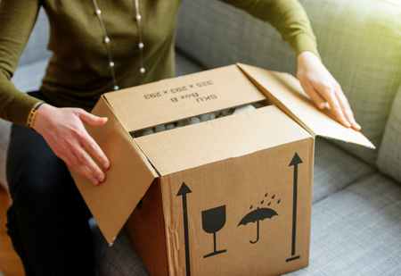 Woman unpacking unboxing cardboard carton box with protective foam pads inside after buying ordering online via internet a present good
