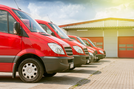 Business row of red delivery and service cars in front of a factory and warehouse distribution plant ready to pick-up the parcels boxes for delivery Reklamní fotografie - 66294128