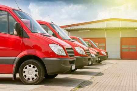 Fila comercial de entrega roja y autos de servicio en frente de una planta de distribución de fábrica y almacén listo para recoger las cajas de paquetes para la entrega Foto de archivo - 66294128
