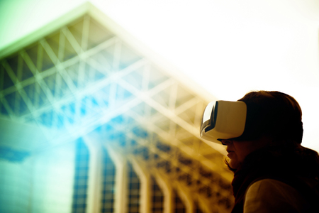handsfree device: VR virtual reality - Woman wearing a virtual reality headset, controlling the experience with hand gesture - looking at green virtual background Stock Photo