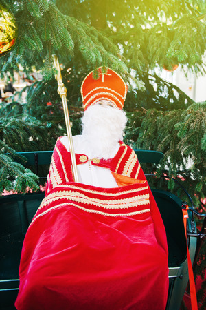LAHR, GERMANY - 30 NOV, 2013: Saint Nicholas human scale toy with mitre and pastoral staff with a fir Christmas tree on background Editorial