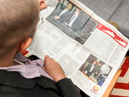newsfeed: PARIS, FRANCE - NOV 12, 2016: Man reading Le Figaro French Entrepreneur newspaper - cover with showroomprive.com first day on stock market Editorial