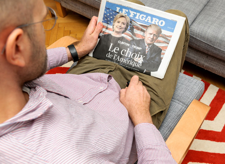 newsfeed: PARIS, FRANCE - NOV 12, 2016: Man reading Le Figaro French newspapper with Hillary Clinton and Donald Trump after Trump has wom the elections