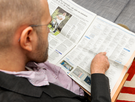 newsfeed: PARIS, FRANCE - NOV 12, 2016: Man reading Le Figaro French newspapper - pointing to Obituaries section of the newspaper